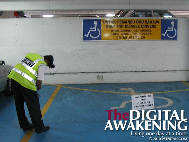 Security personnel unlocking chained up accessible parking at Jusco Kinta City Ipoh