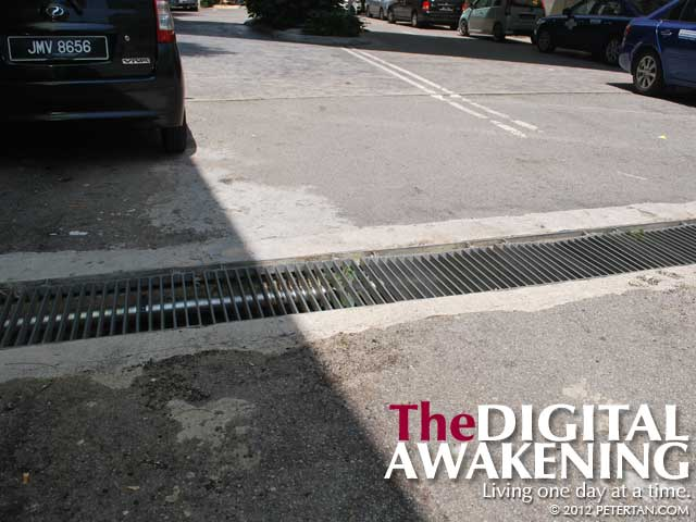 Drain grates with grilles running parallel to the road that endanger wheelchair users